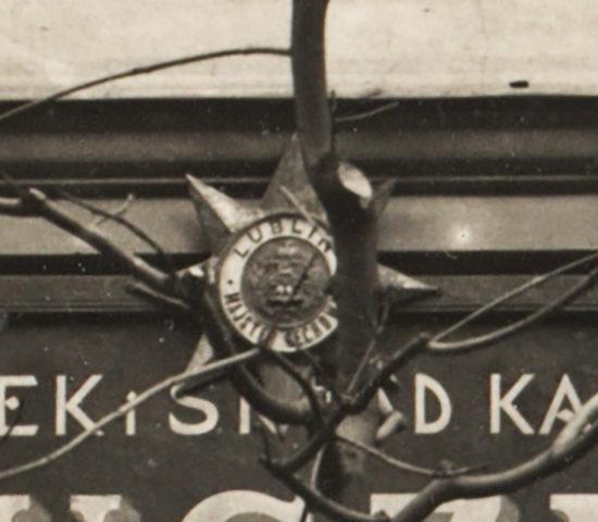 Fragment fotografii frontu pracowni czapniczej i składu kapeluszy S. Januszewskiego przy ul. Kapucyńskiej 2 w Lublinie