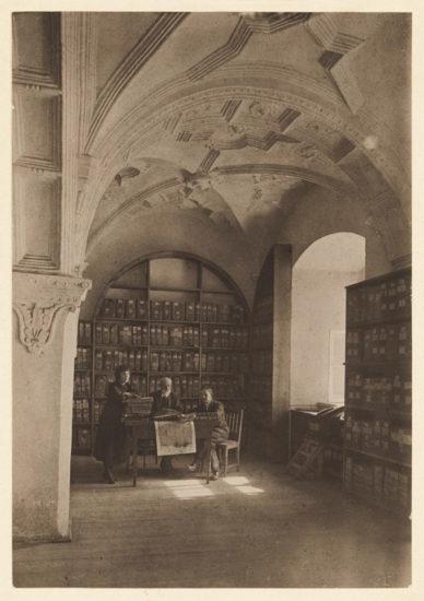 Na fotografii trzy postacie wewnątrz dawnego archiwum